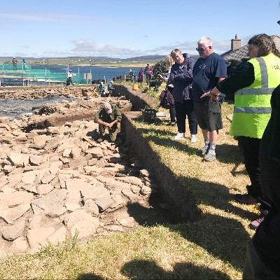 A tour group views Trench J at the Ness of Brodgar.