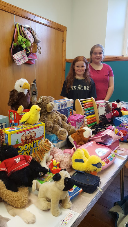table with second hand toys with two smiling girls at coffee morning
