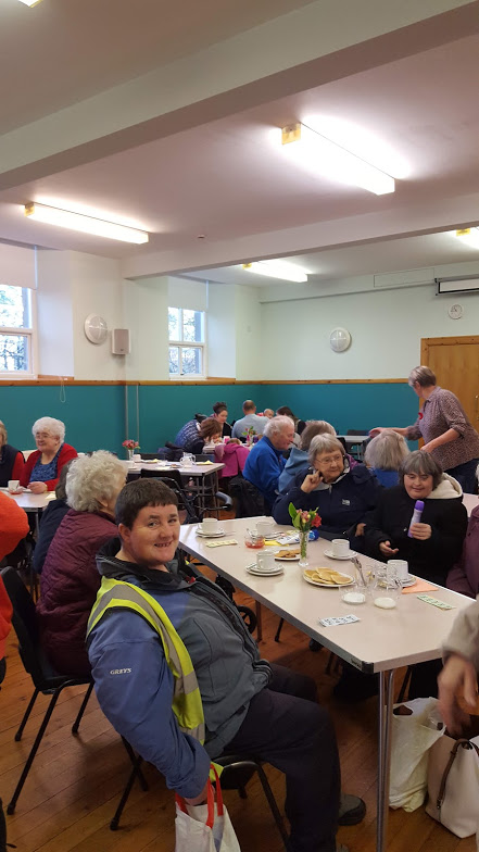 church hall full with happy attendees sitting at table with cakes and tea