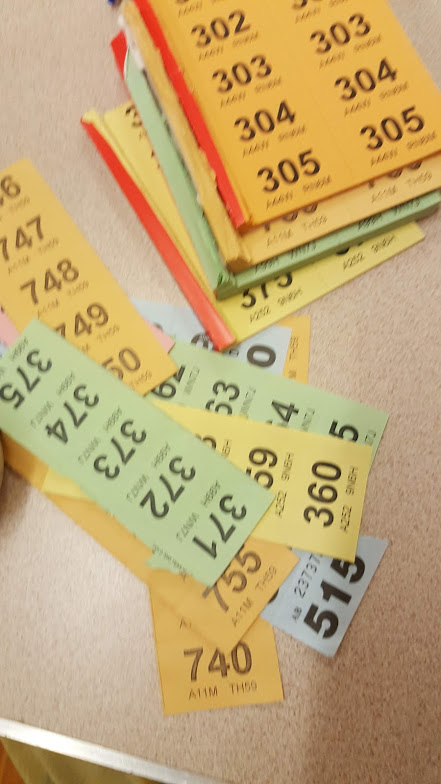 four raffle books in different colors next to a pile of tickets