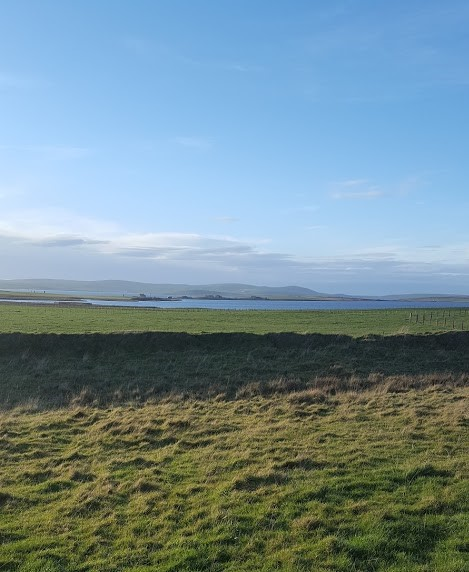 grass field with lochs and stones of stenness in distance