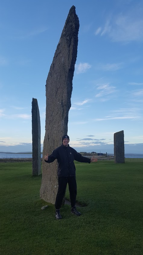 tall man stood infront of stenness stones he is one third the size of the stone