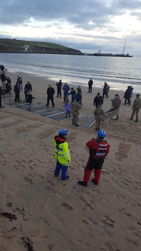 volunteers raking stencils into Scapa beach