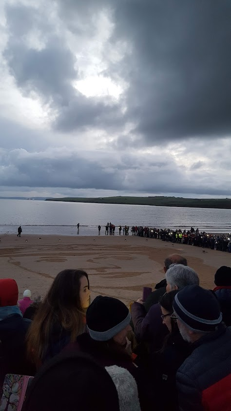 crowd on scapa beach orkney looking at drawing on sand pages of sea