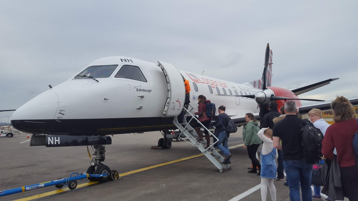 small Logan Air plane on runway passengers boarding