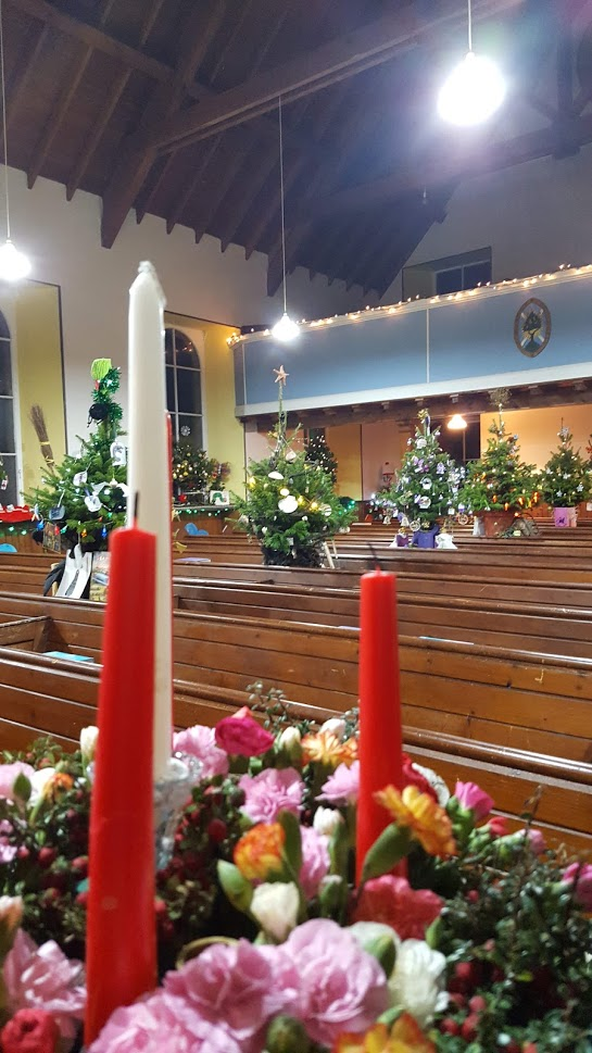 orphir kirk hall this december in orkney with small decorated trees lining up the middle