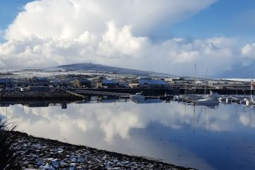Kirkwall marina orkney with snow on the stones and hill in distance