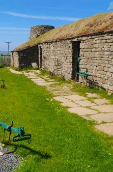 sunny day at the corrigall farm museum ploughs lie on the grass next to stone farmhouse