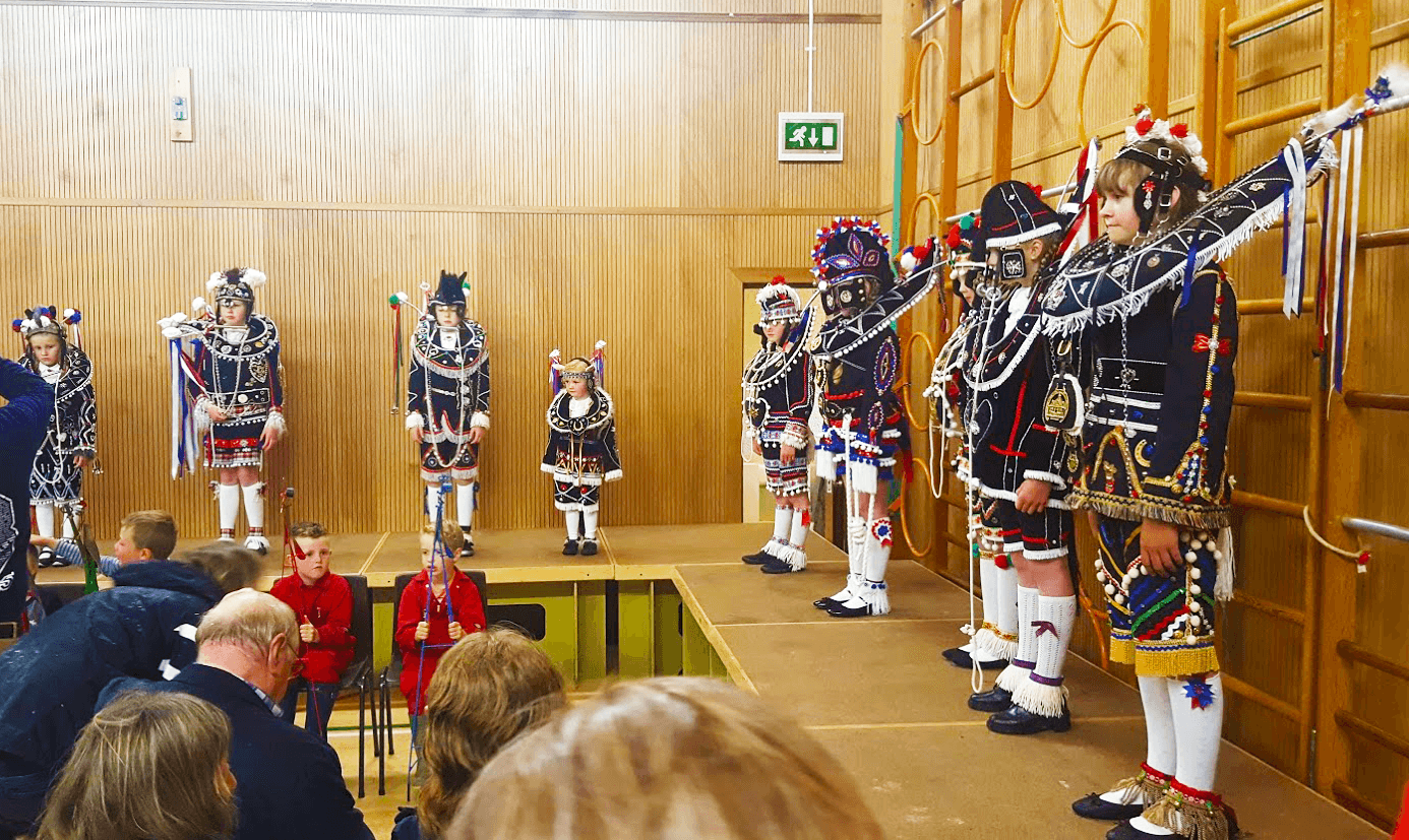 girls in elaborate black and white horse costumes stand on stage in the school hall